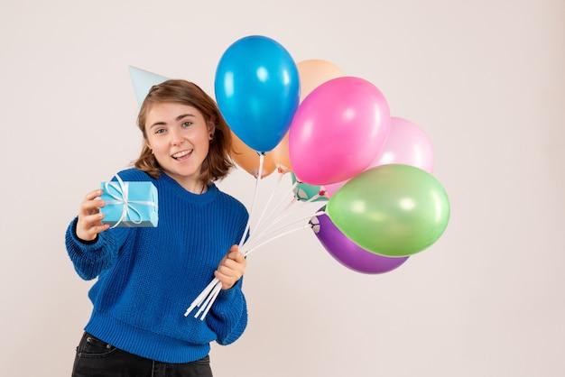 Jeune femme tenant des ballons colorés et peu de cadeau sur blanc