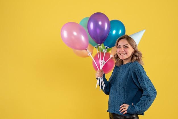 Jeune femme tenant des ballons colorés et souriant sur jaune