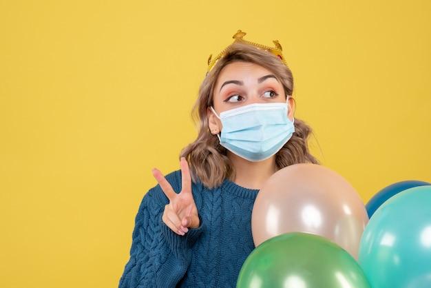 Jeune femme tenant des ballons en masque stérile sur jaune