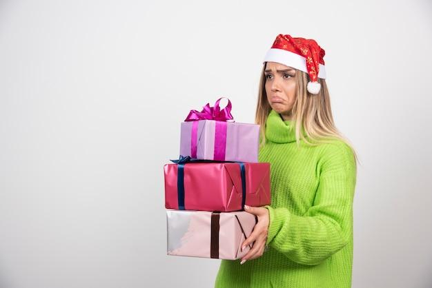 Jeune femme tenant beaucoup de cadeaux de noël festifs