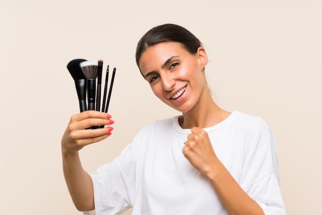 Jeune femme tenant beaucoup de pinceau de maquillage célébrant une victoire