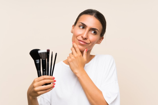 Jeune femme tenant beaucoup de pinceau de maquillage en pensant à une idée