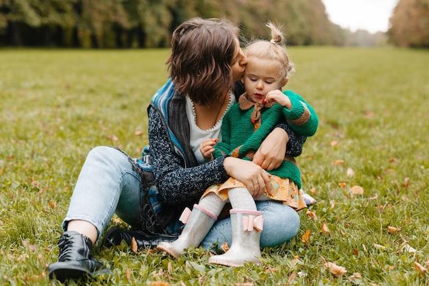 Jeune femme tenant un bébé dans ses bras, assise sur l'herbe dans le parc. maman et sa fille marchent dans le parc.