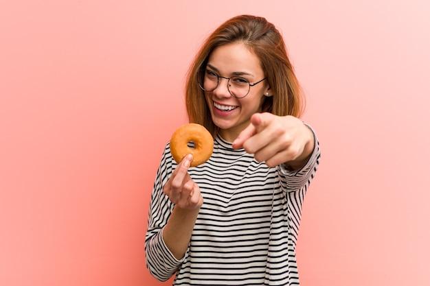 Jeune femme tenant un beignet sourires joyeux pointant vers l'avant.