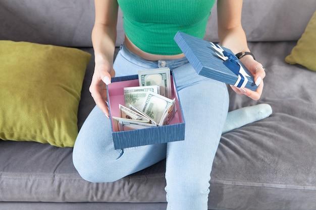 Jeune femme tenant une boîte-cadeau avec de l'argent.