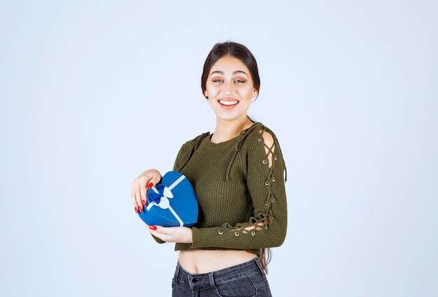 Jeune femme tenant une boîte cadeau bleue avec une expression heureuse.