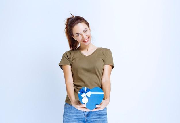 Jeune femme tenant une boîte-cadeau de forme entendue bleue et se sentant satisfaite