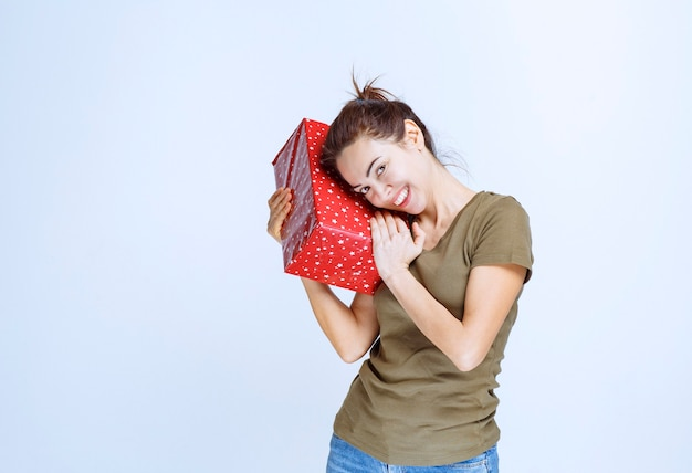 Jeune femme tenant une boîte-cadeau rouge au-dessus et au-dessus de sa tête