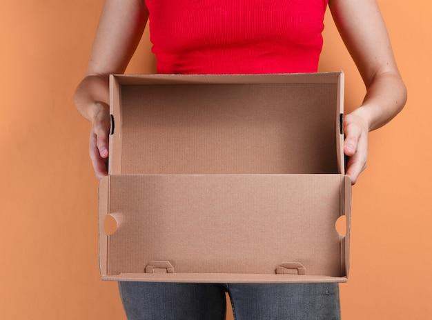 Jeune femme tenant une boîte en carton vide sur orange
