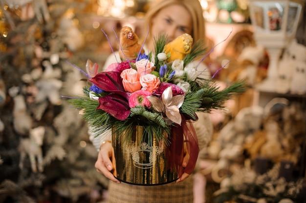 Jeune femme tenant une boîte dorée de roses roses et de lys calla cramoisis