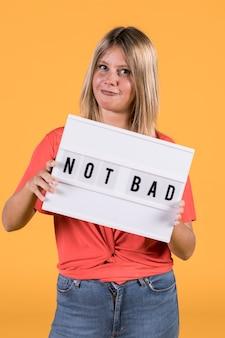 Jeune femme tenant une boîte à lumière blanche avec pas mal de texte