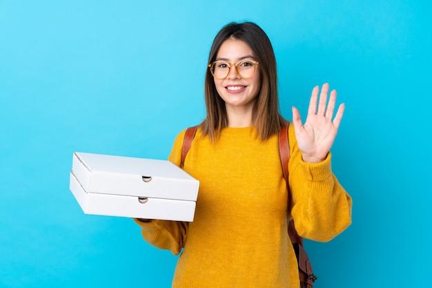 Jeune femme tenant une boîte à pizza sur un mur bleu isolé