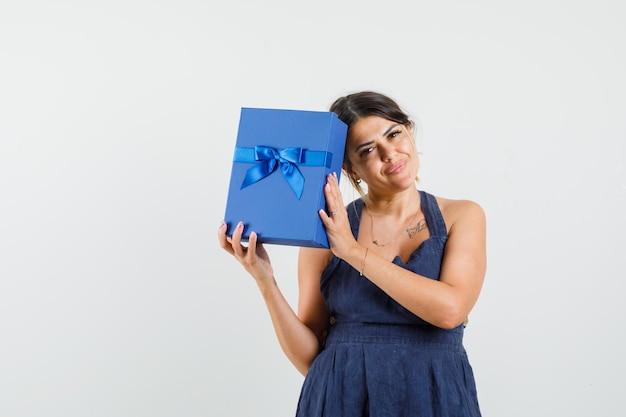 Jeune femme tenant une boîte présente en robe et regardant jolly