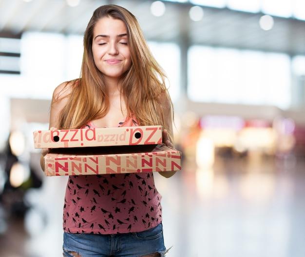 Jeune femme tenant une boîtes à pizza sur fond blanc
