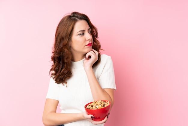 Jeune femme tenant un bol de céréales et de penser