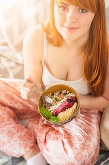 Jeune femme tenant un bol de granola à l'avoine fait maison avec des myrtilles; tranches de framboises et bananes