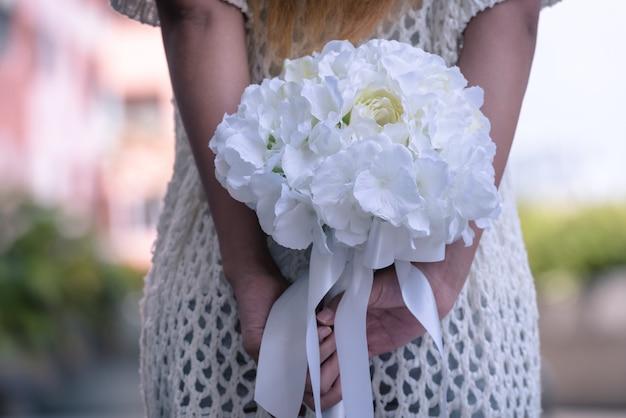 Jeune femme tenant un bouquet de fleurs derrière son dos.