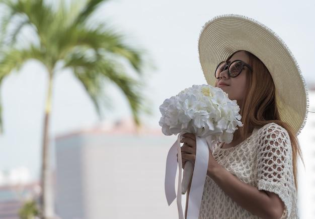 Jeune femme tenant un bouquet de fleurs.