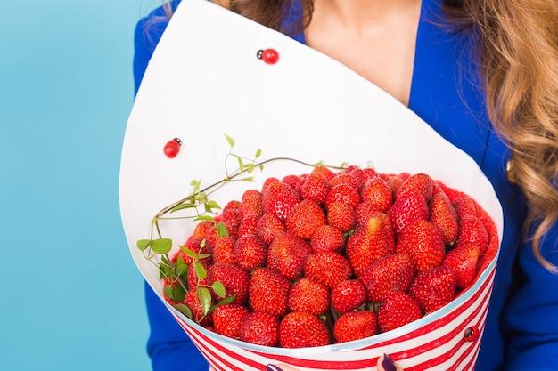 Jeune femme tenant un bouquet de fraises sur fond bleu