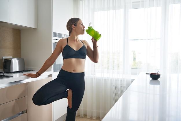 Jeune femme tenant une bouteille de boisson protéinée à table dans la cuisine après une formation à domicile