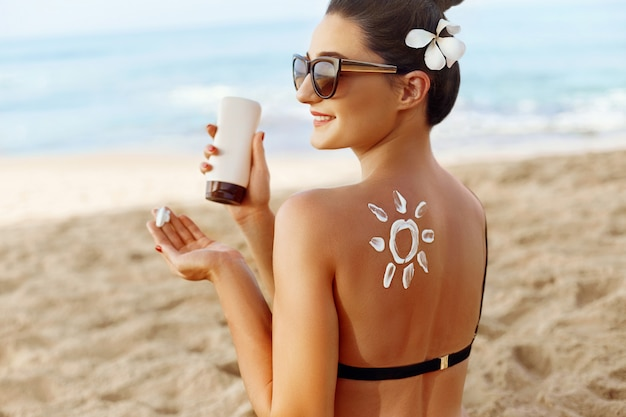 Jeune femme tenant une bouteille de crème solaire et appliquant sur le visage souriant