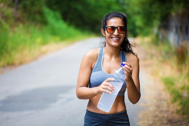 Jeune femme tenant une bouteille dans la forêt
