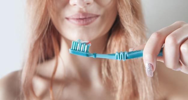 Jeune femme tenant une brosse à dents avant de se brosser les dents.