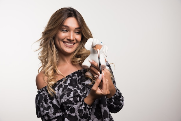 Jeune femme tenant une brosse et un jouet éléphant sur un mur blanc.