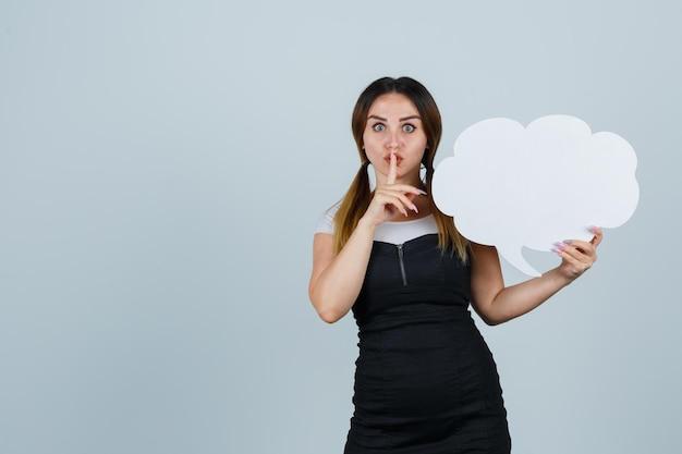Jeune femme tenant une bulle de dialogue tout en montrant un geste de silence