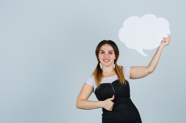Jeune femme tenant une bulle de dialogue tout en montrant les pouces vers le haut