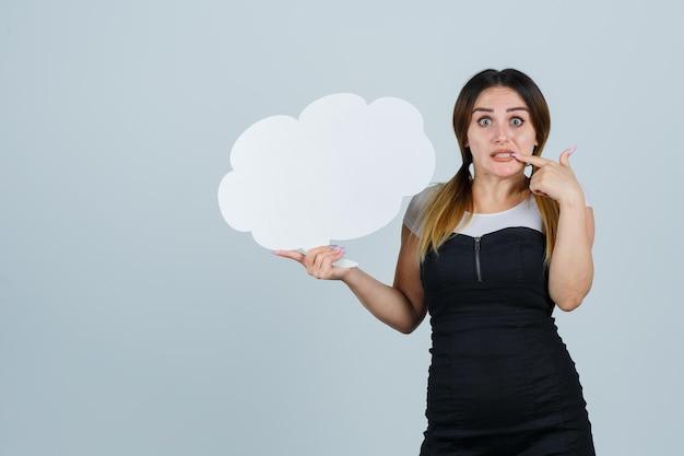 Jeune femme tenant une bulle de dialogue tout en se rongeant les ongles
