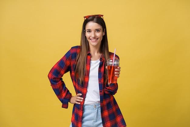 Jeune femme tenant et buvant une boisson fraîche dans des vêtements décontractés. jolie fille souriante heureuse en riant en regardant la caméra.