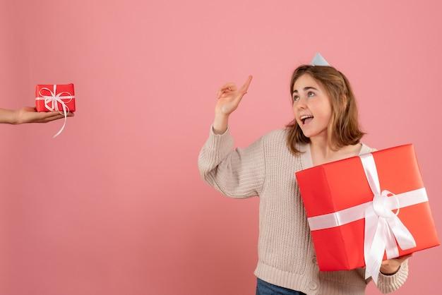 Jeune femme tenant un cadeau de noël et acceptant un cadeau d'un homme sur rose