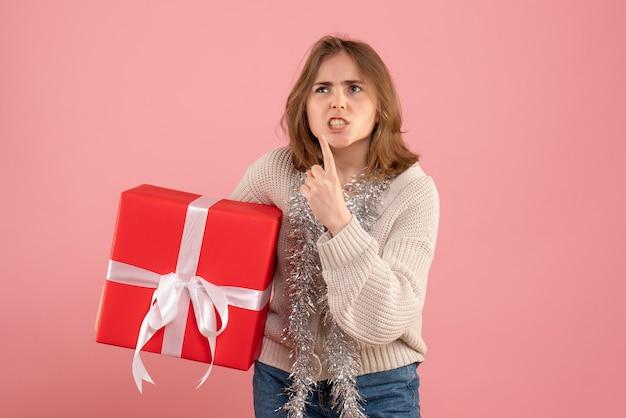 Jeune femme tenant un cadeau de noël dans ses mains sur rose