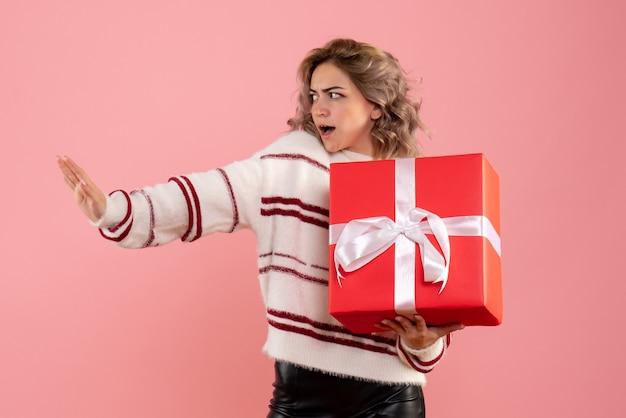 Jeune femme tenant un cadeau de noël sur rose