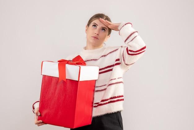 Jeune femme tenant un cadeau rouge sur blanc