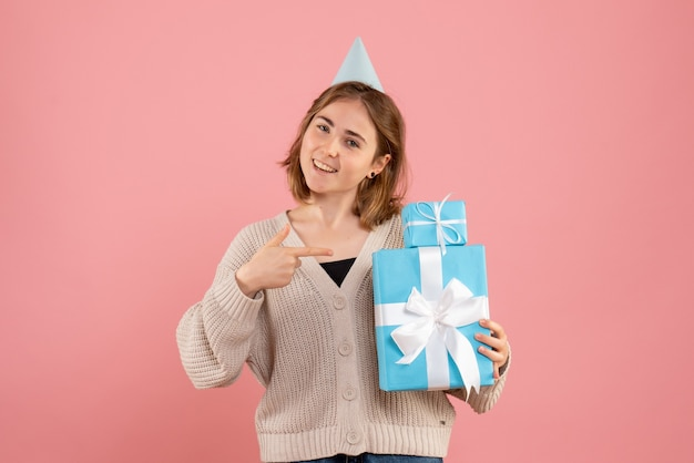 Jeune femme tenant des cadeaux de noël sur rose