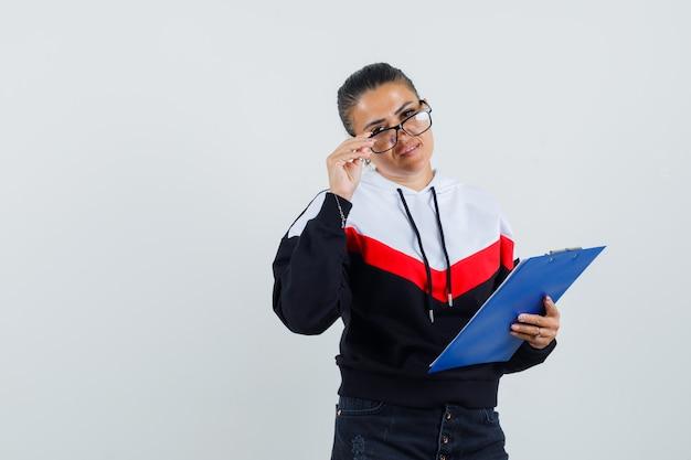 Jeune femme tenant un cahier tout en décollant des lunettes en pull, jeans noirs et à la jolie. vue de face.