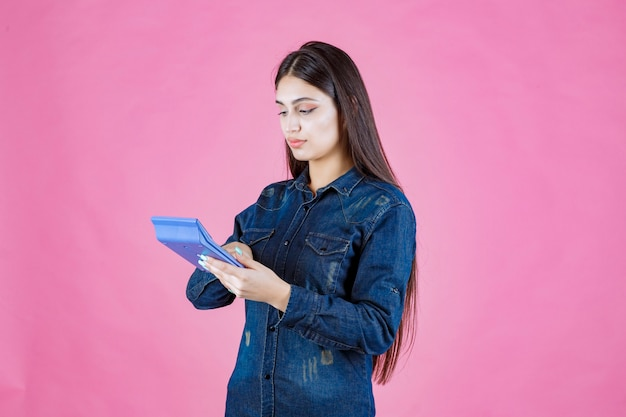 Jeune femme tenant une calculatrice bleue dans la main et calcul