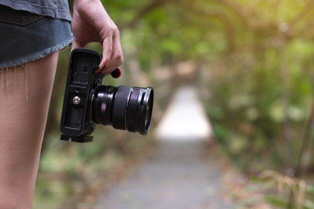 Jeune femme tenant la caméra, concept de photographe