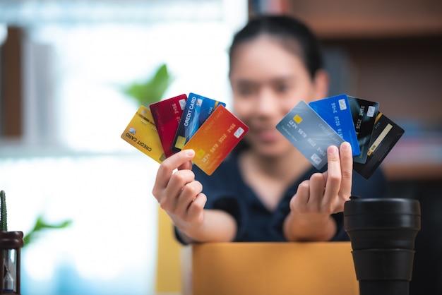 Jeune femme tenant une carte de crédit et à l'aide d'un ordinateur portable. concept d'achat en ligne