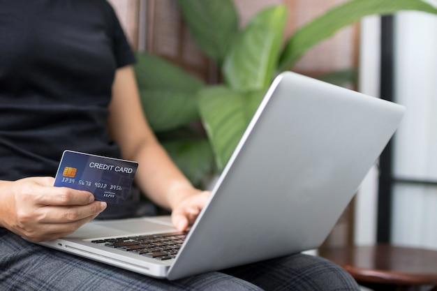Jeune femme tenant une carte de crédit et à l'aide d'un ordinateur portable. concept de magasinage en ligne. espace de copie.