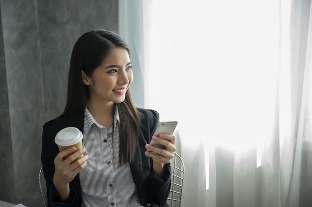 Jeune femme tenant la carte de crédit, magasinage en ligne de l'ordinateur portable.