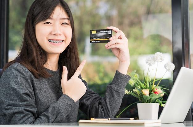 Jeune femme tenant une carte de crédit avec un ordinateur portable sur le pont