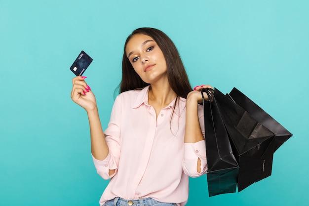 Jeune femme tenant une carte de crédit et des sacs noirs et souriant. concept de vendredi noir.