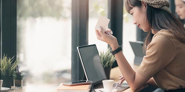 Jeune femme tenant une carte de crédit et utilisant un ordinateur portable. concept d'achat en ligne.