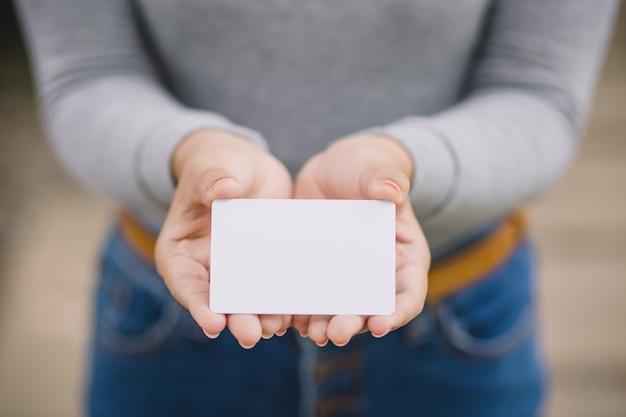 Jeune femme tenant une carte de crédit vierge, en plein air