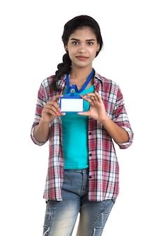 Jeune femme tenant une carte d'identité en plastique vierge d'identification blanc.