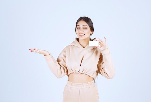 Jeune femme tenant une carte de visite et pointant vers quelqu'un
