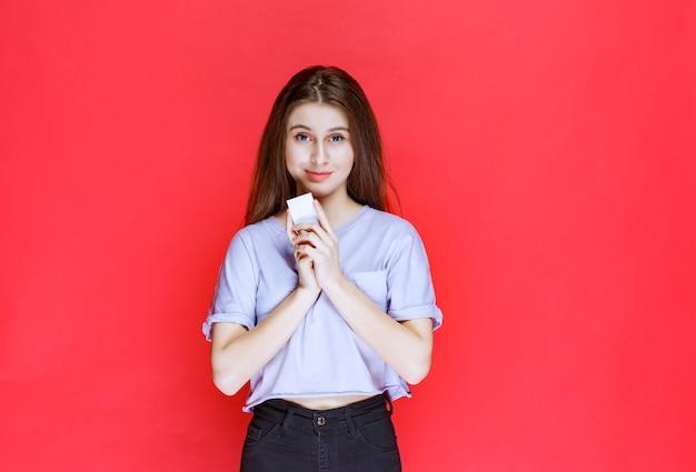 Jeune femme tenant une carte de visite et se présentant.